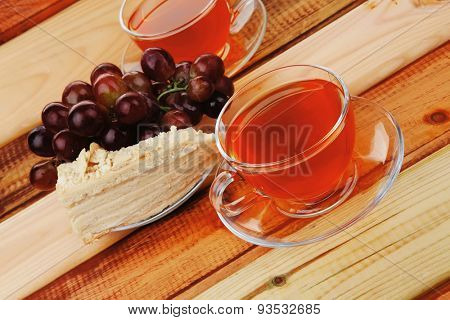 cream cake with tea and grapes on wood