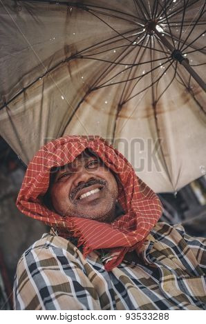 MUMBAI, INDIA - 10 JANUARY 2015: Man smiling and sitting under a parasol