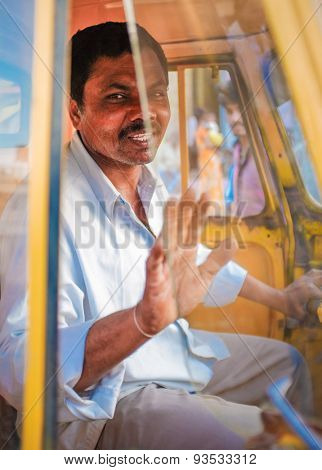 KAMALAPURAM, INDIA - 02 FEBRUARY 2015: Indian delivery man gesticulating while passing by in a three-wheeler