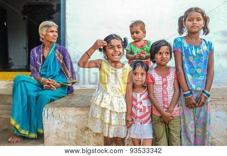 HAMPI, INDIA - 31 JANUARY 2015: Indian family members standing infront of house. Grandmother overlooking her five grandaughters