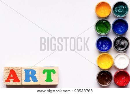 Art word formed by wood alphabet blocks with colorful gouache paints on white background