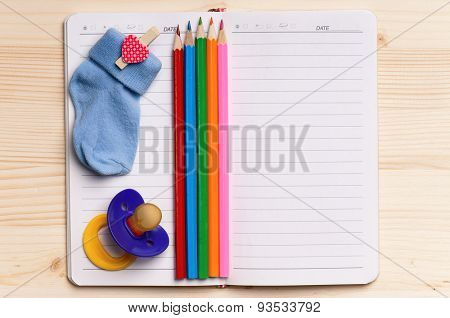 Blank notebook with colorful pencils - top view