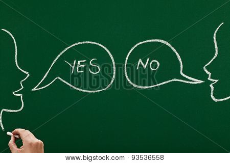 two faces on blackboard one saying no and the other one yes