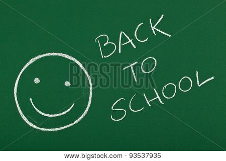 smiley with back to school message on blackboard