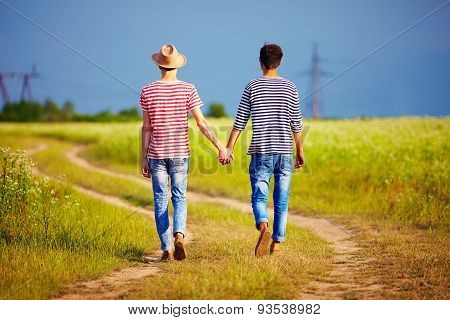 Young Male Couple Walking Away On Summer Field Path