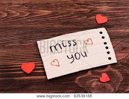 Inscription MISS YOU on cutout carton on wooden background
