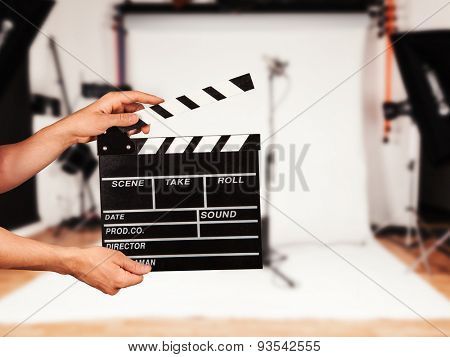 Man hands holding film clapper. Blur film studio on background