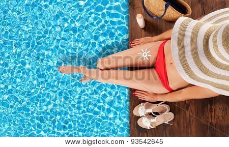 Young woman relaxing and sunbathing at swimming pool, sitting on wooden planks