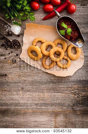 fried onion rings on parchment with sauce and vegetables on a wooden background
