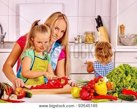 Mother and daughter cooking vegetarian food at kitchen.