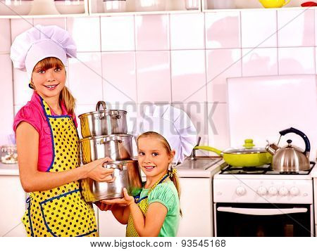 Children wearing hats and aprons  cooking at kitchen along.