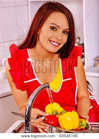 Happy woman washing vegetable at kitchen.