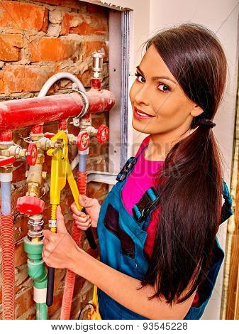 Woman  builder fixing heating system with special tool and happy smiling.