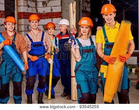 Happy group people men and women in builder uniform.