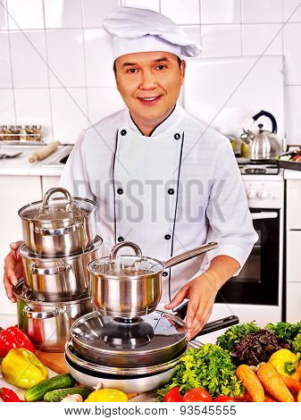 Man in chef hat cooking at professional kitchen.