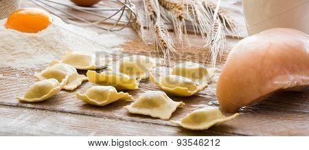 Ravioli and chicken breast on a flour board
