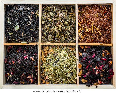 aromatic dry teas in wooden box and spoons on wooden background