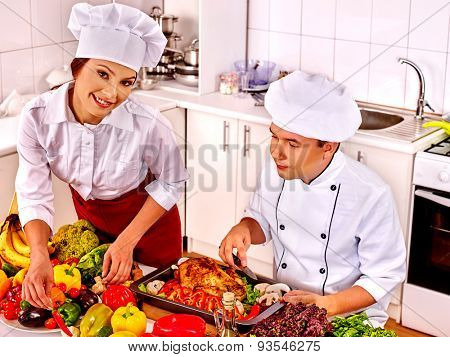Happy man and woman in chef hat cooking chicken.