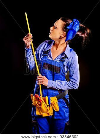 Happy woman builder with construction tools on dark background.