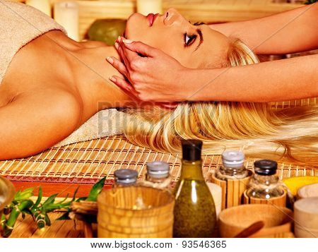 Woman getting facial massage in tropical beauty spa. Visible hand
