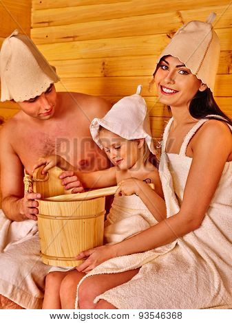 Family with one kid in hat  relaxing at sauna