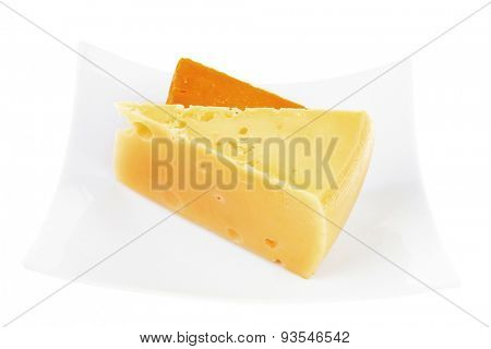 cheese : french gourmet triangles of yellow parmesan and orange cheddar on a plate isolated over white background