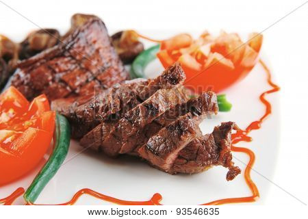 fillet mignon served on a white plate with tomatoes