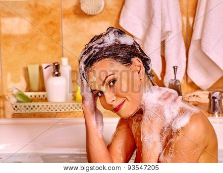 Happy woman washing hair in bubble bath.