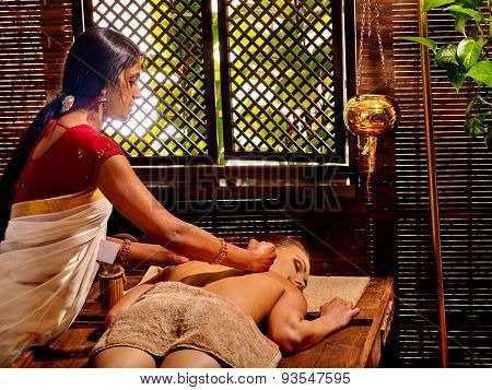 Young woman having oil Ayurveda spa treatment. Day outdoor.