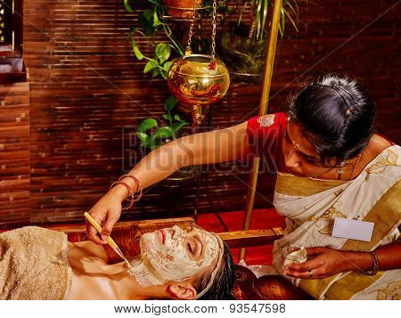 Woman having clay Indian facial mask at ayurveda spa.