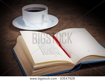 Open book with a cup of coffee on wooden table