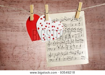 Bright hearts and music sheet hanging on rope on wooden background