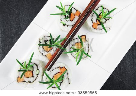 Maki Sushi - California Roll with Cucumber , Cream Cheese and Salmon inside. Served with wasabi and ginger . on long white plate over black table