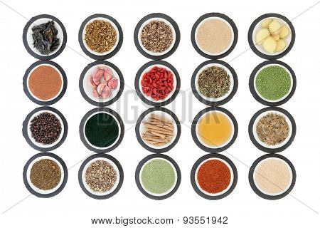 Immune boosting health super food selection in porcelain dishes on slate rounds over white background.
