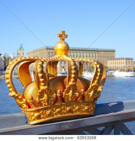 Crown on a bridge railing in Stockholm and Royal Palace in the background, Sweden