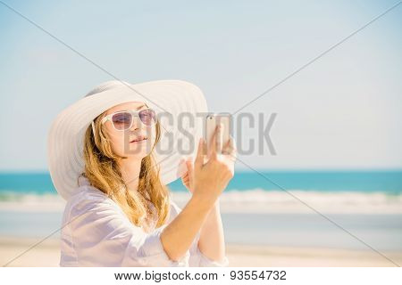 Beautifil young woman sitting on the beach at sunny day with phone in her hand