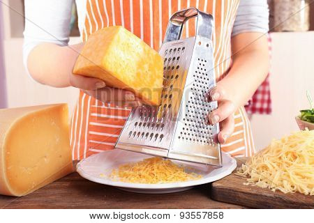 Closeup of female hands grating cheese