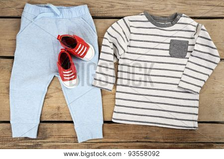 Clothes for baby boy on wooden background