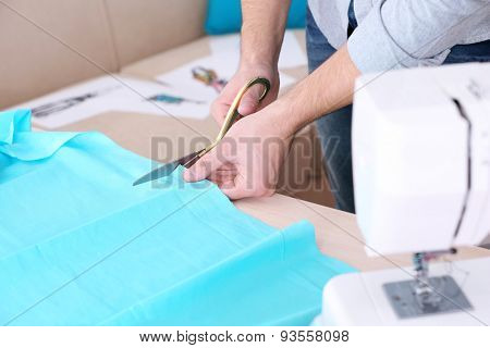 Male dressmaker cut fabric on table