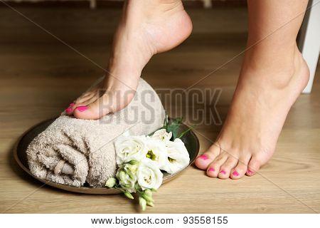 Beautiful female legs on towel, wooden floor background