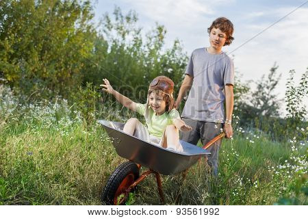 two friends playing in the plane using a garden carts