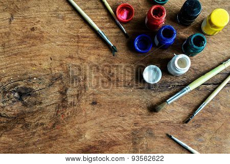 Paintbrush And Poster Color On Old Wood Background