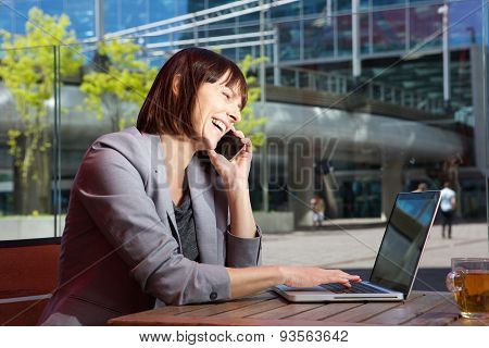 Happy business woman talking on mobile phone and working on laptop