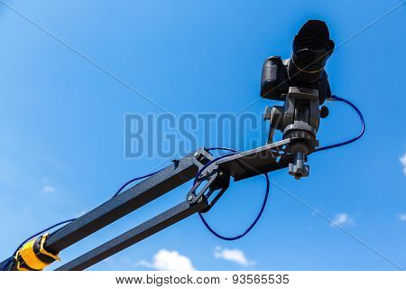 Camera On A Crane On A Blue Sky Background