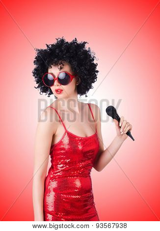 Pop star with mic in red dress against the gradient