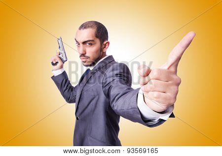 Businessman with gun against the gradient