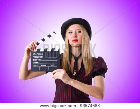 Woman gangster with movie board against the gradient