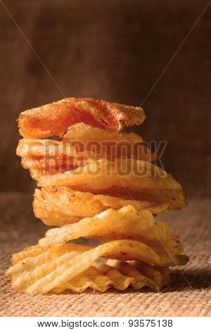 A stack of potato chips with warm side light. Vertical format on a burlap surface.