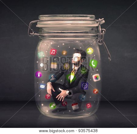 Businessman captured in a glass jar with colourful app icons concept on background