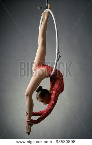 Graceful acrobat performs gymnastic trick on hoop